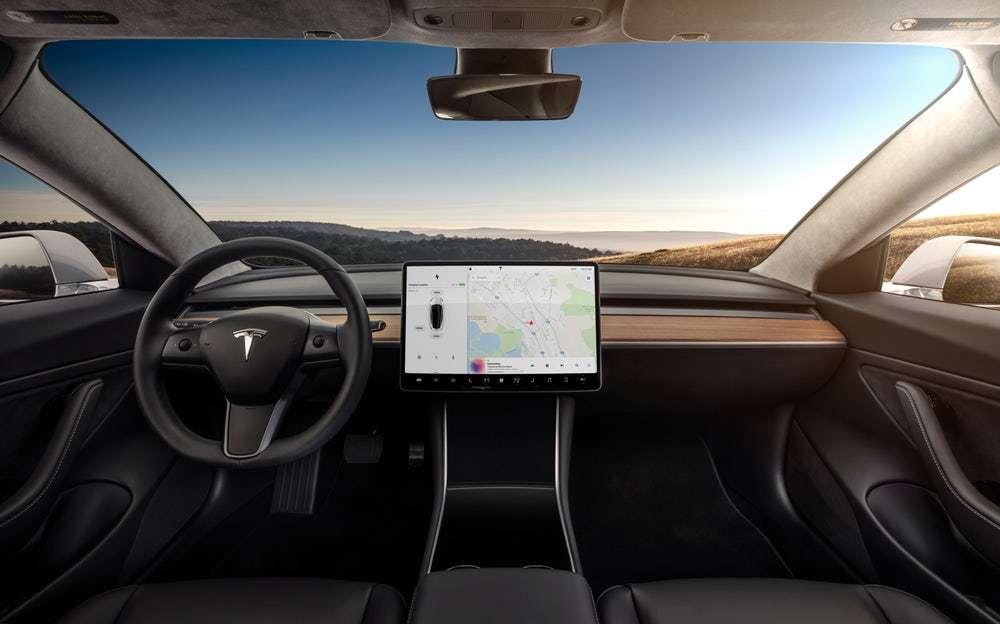 L'intérieur de la Tesla Model 3 pousse encore un peu plus loin le minimalisme du design du tableau de bord. Aucun bouton : tout se passe sur l'écran tactile central. On constate également l'absence des grilles de ventilation, remplacées par un système qui couvre toute la longueur avec des ailettes cachées et « deux plans d'air croisés pour le contrôle vertical », dixit Elon Musk. © Tesla