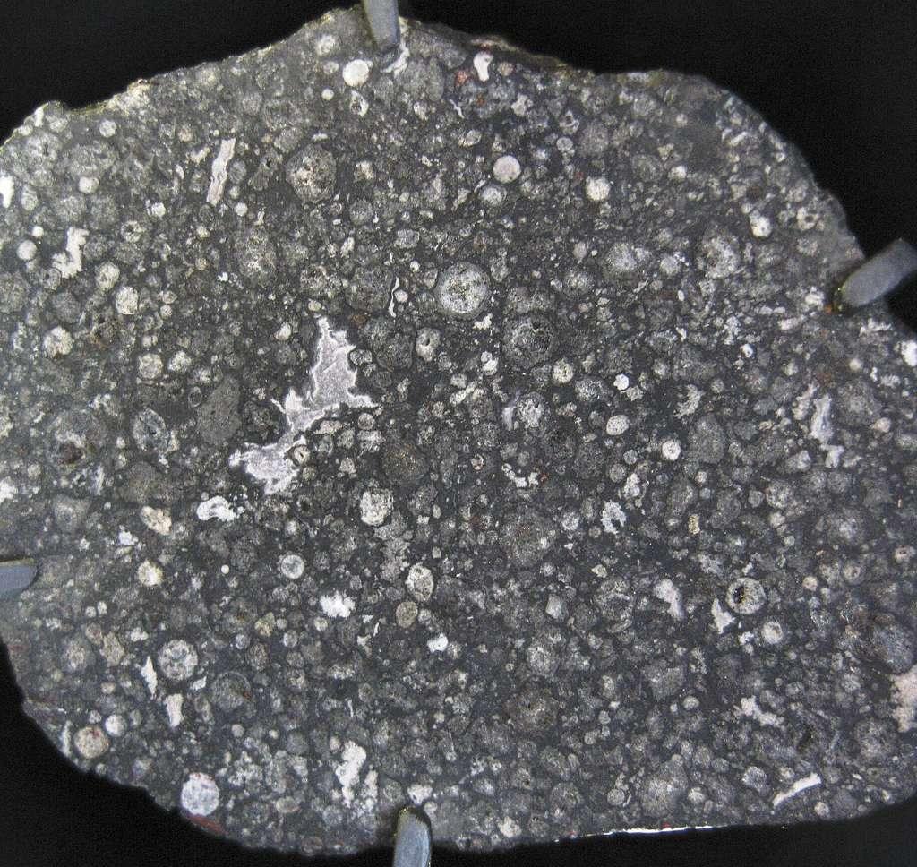 Une coupe de la célèbre météorite Allende. Cette chondrite carbonée contient des structures irrégulières blanchâtres, des CAI (pour Calcium-Aluminum-rich Inclusions, en anglais). Leur formation date de 4,568 milliards d'années et elles contiennent des traces de radioactivités éteintes. © CC by 20, Shiny Things