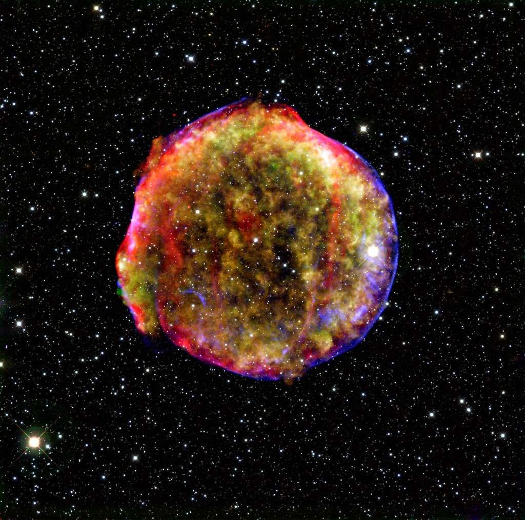Le 11 novembre 1572, Tycho Brahe observait l'explosion d'une étoile à 1.500 années-lumière de nous dans la constellation de Cassiopée. Il s'agissait d'une supernova, et l'on sait maintenant qu'elle était de type SN Ia, donc associée à l'explosion d'une naine blanche. On voit sur cette image composite le reste de la supernova SN 1572, dite aussi supernova de Tycho. © Rayons X : Nasa, CXC, SAO ; infrarouge : Nasa, JPL-Caltech ; optique : MPIA, Calar Alto, O. Krause et al.