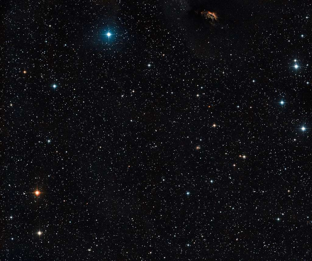 Cette vue étendue montre le ciel qui entoure le jeune système d'étoiles multiples GG Tauri, situé à proximité du centre de l'image. Les astronomes y voient également un nuage de poussière ainsi que la preuve de la formation d'étoiles dans la partie supérieure de l'image – GG Tau fait partie intégrante du Nuage sombre du Taureau. © Eso, DSS2, David De Martin