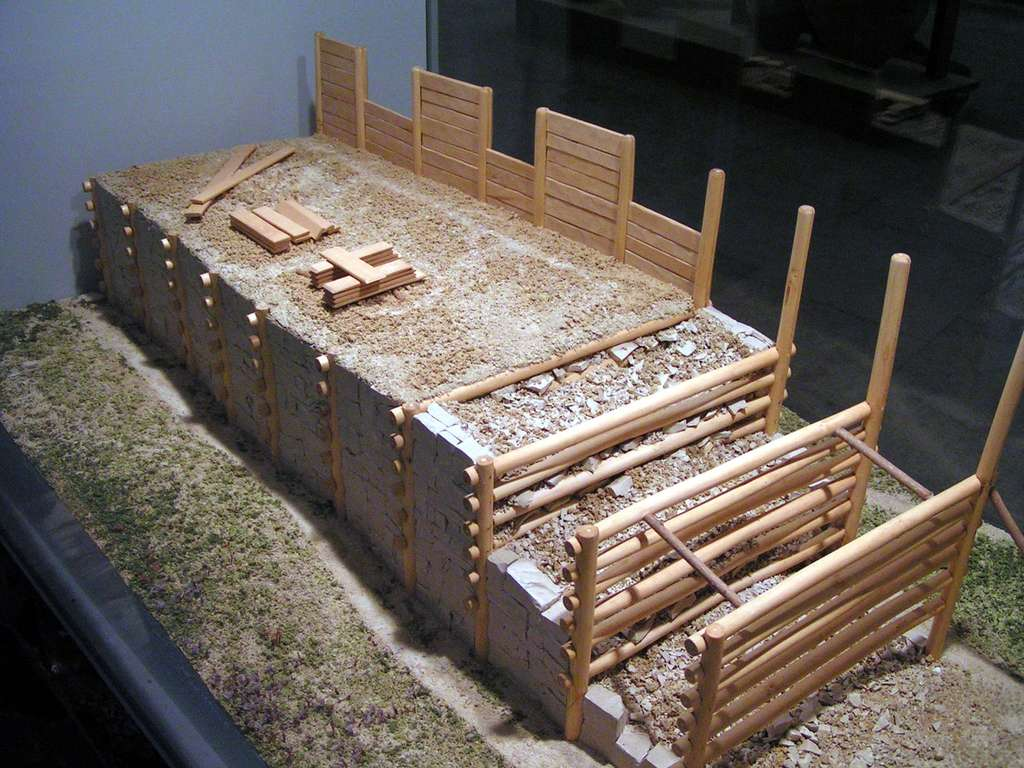 Le murus gallicus est une construction en terre, rendue plus solide grâce à un empilement de couches entrecroisées de poutres horizontales. Un parement de pierre sèche vient recouvrir le tout. © Stefan Kühn, GNU FDL 1.2