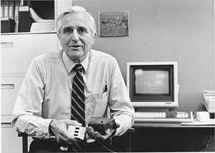 En 1968, Douglas Engelbart présente son prototype de souris (dans sa main gauche) et un modèle à trois boutons (dans sa main droite). © SRI