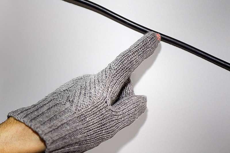 Une LED intégrée dans le bout du doigt d'un gant s'éclaire lorsqu'elle s'approche d'un câble électrique alimenté. © Purdue University