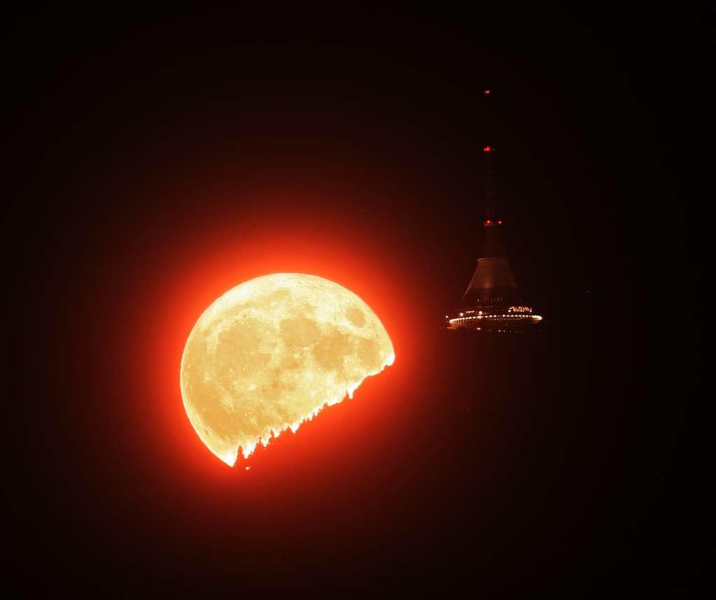 Non, ce n'est pas une soucoupe volante à droite, devant la super Lune qui se lève mais l'hôtel Ještěd, à Brevniste, en République tchèque. © Martin Gembec