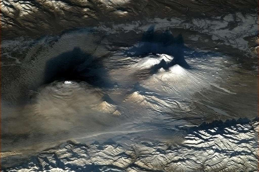 À gauche dans les nuages, le volcan Tolbatchik. Au fond de l'image à droite, le volcan bouclier Ushkovsky. Devant lui, le Kliouchevskoï. En avant-plan, deux volcans de taille plus modeste. © Nasa, CSA, Chris Hadfield