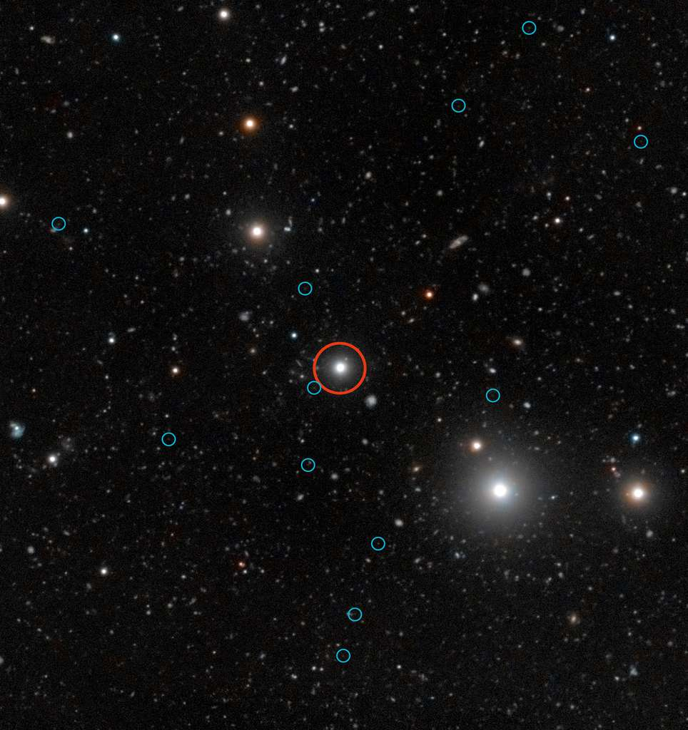 Cette image profonde montre une région du ciel autour du quasar HE0109-3518. Le quasar est repéré par un cercle rouge à proximité du centre de l'image. Le rayonnement énergétique du quasar fait briller les galaxies noires, aidant ainsi les astronomes à comprendre les phases primordiales obscures de la formation des galaxies. Les images faibles du rayonnement de 12 galaxies noires sont indiquées par des cercles bleus. Les galaxies noires sont pratiquement dénuées d'étoiles et, de ce fait, elles n'émettent aucune lumière que les télescopes peuvent capter. Elles sont ainsi pratiquement impossibles à observer à moins qu'elles ne soient illuminées par une source lumineuse extérieure comme un quasar en arrière-plan. Cette image combine des observations faites avec le VLT, dédiées à la détection d'émissions fluorescentes produites par un quasar illuminant les galaxies noires, avec des données couleur provenant du Digitized Sky Survey 2. © ESO, Digitized Sky Survey 2, S. Cantalupo (UCSC)