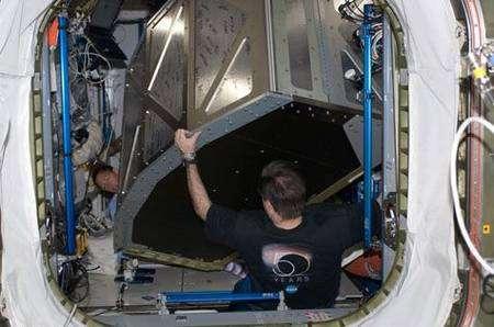 Greg Chamitoff, spécialiste de mission, déplace une cabine de repos que vient de livrer l'équipage d'Endeavour vers le module Harmony. Remarquez les nombreuses signatures sur la paroi du caisson. Cliquer pour agrandir. Crédit Nasa