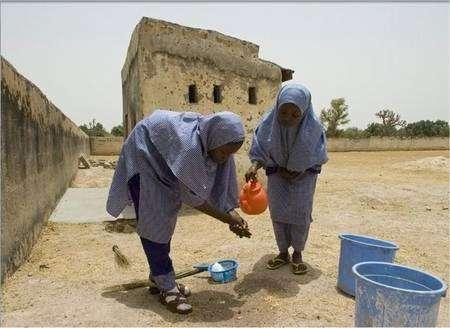 Hafsatu Garba, 13 ans, qui vient de sortir des toilettes de son école, se lave les mains, aidée par une amie. La scène se déroule à Konkiyel Village, au Nigeria. © Unicef/HQ07/Chrstine Nesbitt