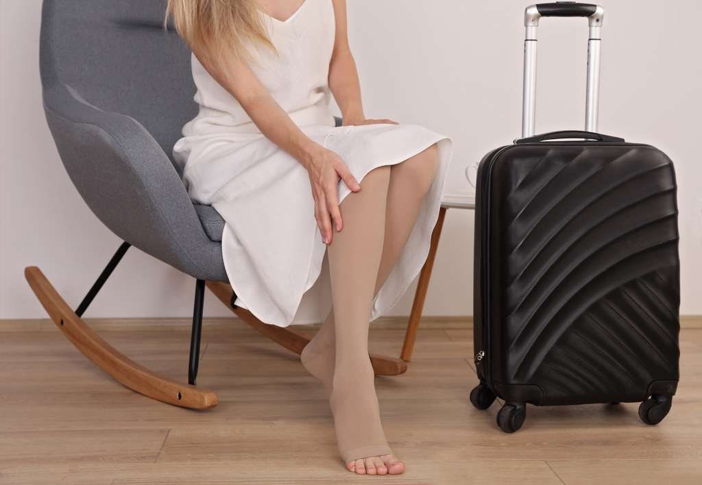 Porter des bas de contention est conseillé aux personnes souffrant d'insuffisance veineuse et peut aussi être recommandé de façon préventive lors d'un long voyage. © glisic_albina, Adobe Stock