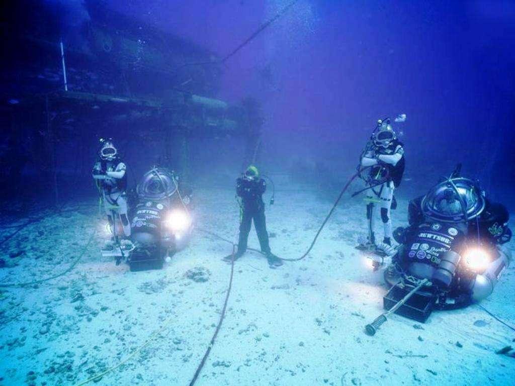 Des aquanautes de la mission Neemo 14 au fond de l'océan Atlantique. La base sous-marine Aquarius est visible en haut à gauche de l'image. © Nasa