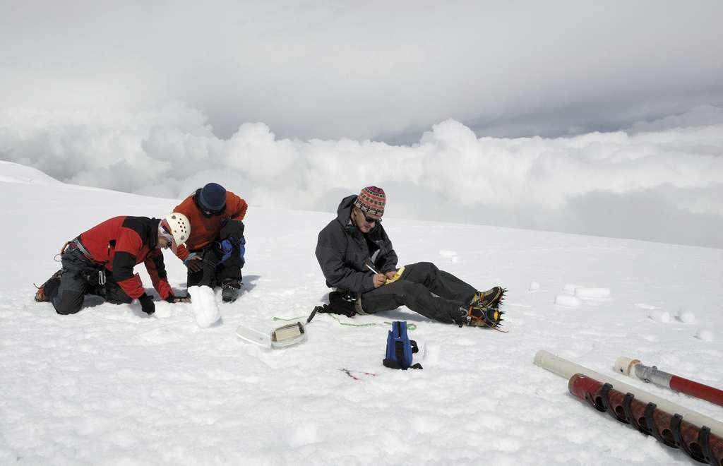 Mesures en zone d'accumulation. À 5.400 m, sur le glacier Antizana, en Équateur, le glaciologue Bernard Francou évalue la densité de la glace et de la neige du carottage. © Bernard Francou