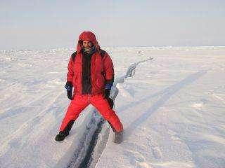 Julien Cabon à cheval entre deux plaques de glace. La banquise n'est qu'une pellicule glacée, de 1 à 2 mètres d'épaisseur, craquelée et perpétuellement en mouvement. © Pôle Nord 2012