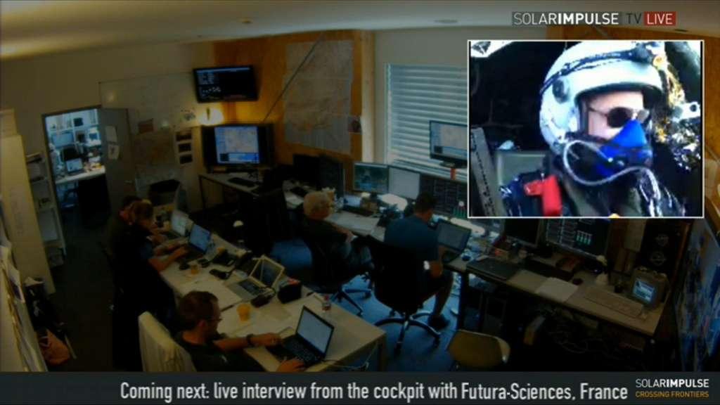 Une vue de la salle de contrôle de Solar Impulse, à Payerne, diffusée sur le site Web. En médaillon, Bertrand Piccard, en train de respirer de l'oxygène. L'avion solaire HB-SIA vole, ce mardi 17 juillet au matin, à un peu moins de 4.000 m d'altitude et le pilote s'offre régulièrement un petit quart d'heure d'oxygénation. En attendant l'interview... © Solar Impulse