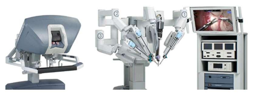 Le robot chirurgien, Da Vinci S, est constitué de gauche à droite d'une console de commande, de plusieurs bras articulés dotés de pinces, et d'une colonne d'endoscopie. © Intuitive Surgical