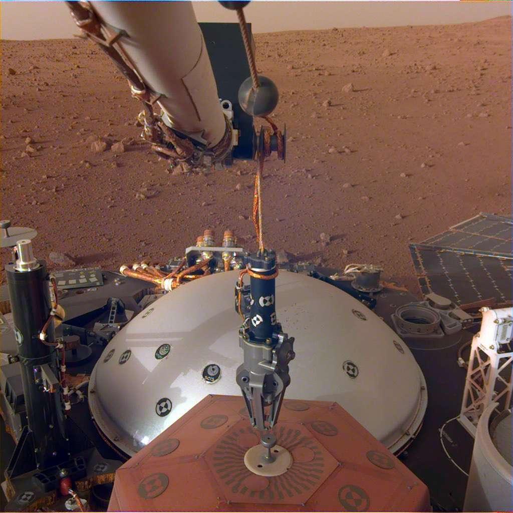 Le bras robotique d'InSight, avec son grappin, s'apprête à saisir le sismomètre français Seis pour le poser sur le sol. © Nasa, JPL-Caltech