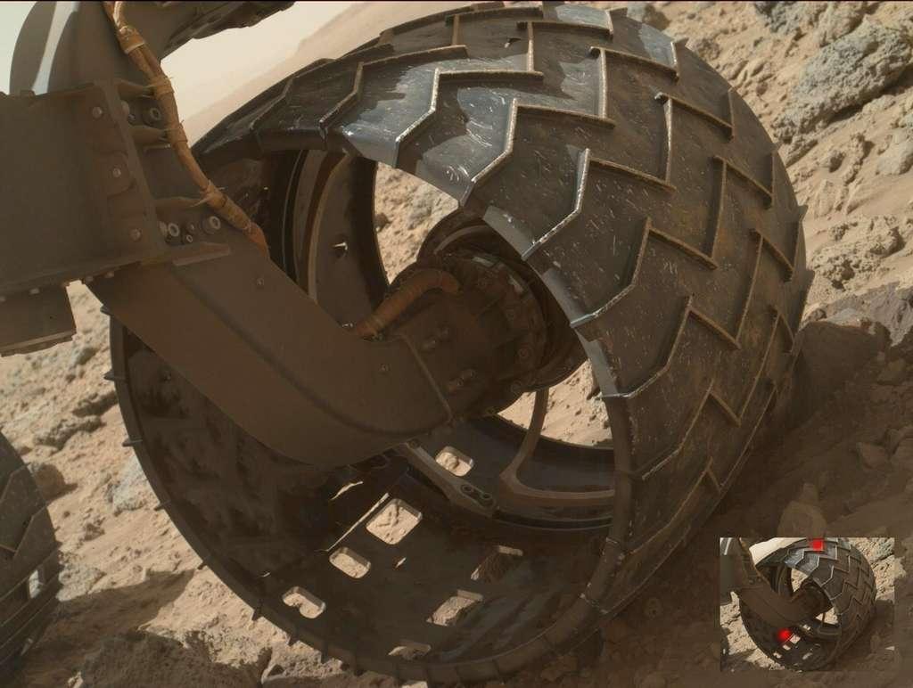 Une des roues mal en point du rover Curiosity. Les marques rouges sur la petite image indiquent deux perforations dont une déchirure, en bas, plutôt inquiétante. © Nasa/JPL