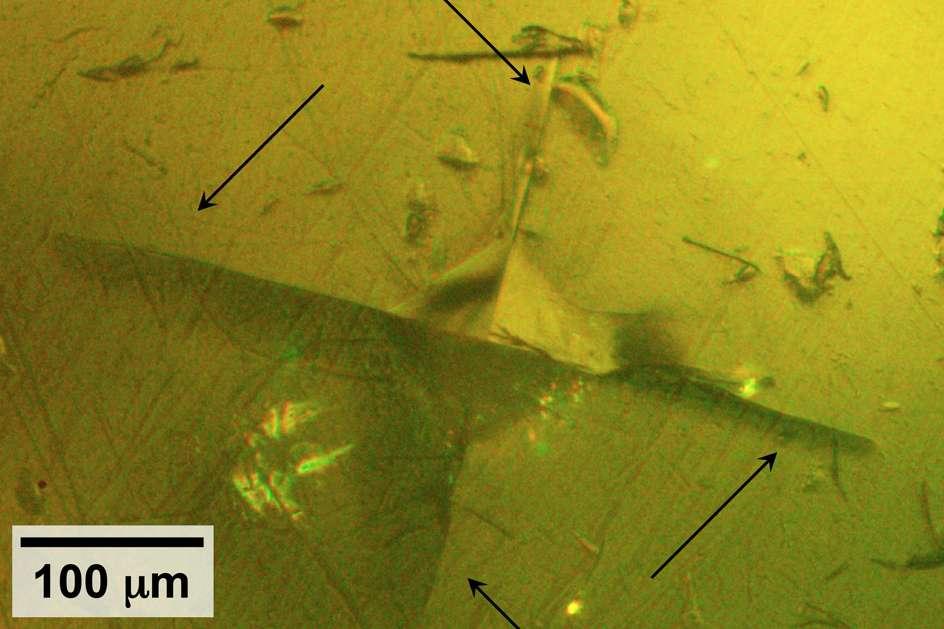 Sur cette image, on observe, au centre, l'impact de la sonde utilisée par les chercheurs du MIT pour tester les propriétés mécaniques du sulfure de lithium. Les flèches pointent les fissures qui se sont formées dans le matériau. © MIT