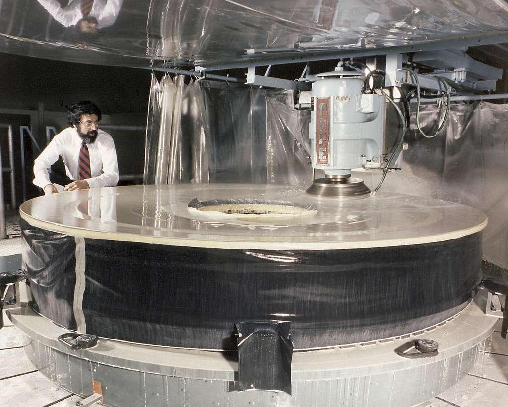 Sur cette image, le miroir principal du télescope spatial Hubble dans l'usine de fabrication d'optiques Perkin-Helmer Coroporation. Plus d'une décennie avant que son minuscule — mais non moins important — défaut ne soit découvert. © Nasa