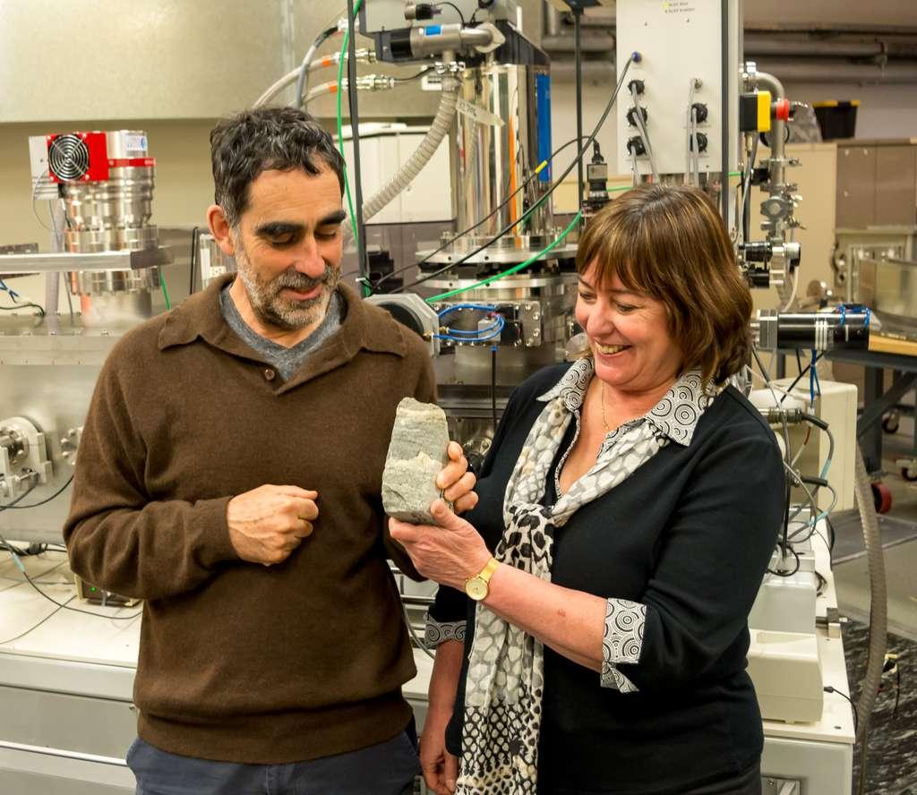 Allen Nutman et Vickie Bennett tenant un des échantillons où l'on peut observer un cône peut-être laissé par un biofilm constitué de cyanobactéries il y a 3,7 milliards d'années. © Yuri Alemin