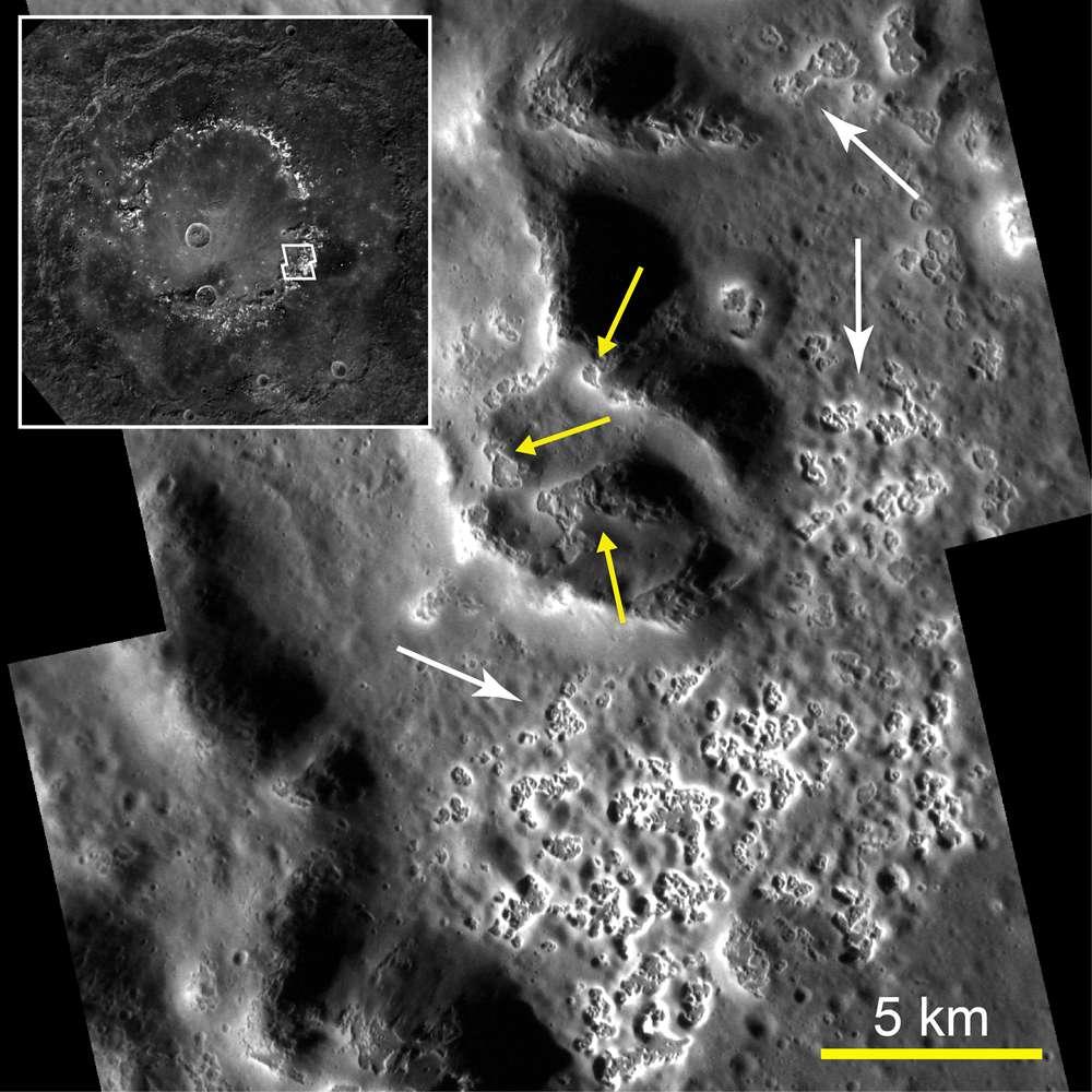 Cette image montre une portion de l'intérieur du bassin Raditladi. L'encart indique l'emplacement de l'image principale. Le sol (flèches blanches) et des anneaux de pics (flèches jaunes) présentent des exemples étonnants de « creux » (Hollows en anglais), une forme de relief inattendu que montrent les images haute résolution. Ces creux sont des dépressions peu profondes, irrégulières et brillantes dont la formation peut impliquer la perte de matières volatiles. © Science/AAAS