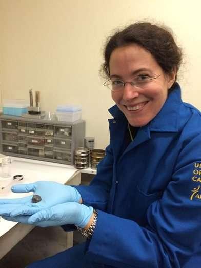 La géochimiste Mélanie Barboni avec un fragment de roche lunaire. Avec ses collègues, elle a utilisé une technique de spectrométrie de masse par ionisation thermique et dilution isotopique (ID-TIMS pour l'anglais Isotope Dilution et Thermal Ionization Mass Spectrometry) pour étudier huit zircons présents dans des roches ramenées en 1971 par la mission Apollo 14. © Mélanie Barboni, UCLA