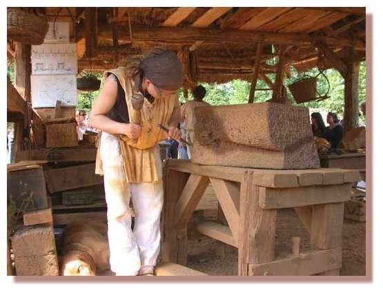 Tailleur de pierre. Tailleur de pierre en train de sculpter un coussinet en grès ferrugineux qui sera placé en surplomb d'une archère dans la salle de tir de la tour maîtresse. © Photo Guédelon