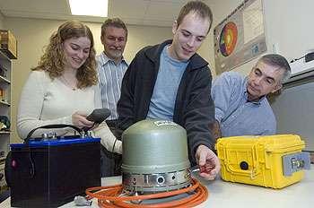 L'équipe de Douglas Wiens (derrière) vérifiant un sismographe destiné aux observations en Antarctide. © David Kilper