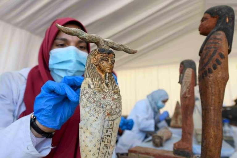 Une archéologue nettoie des statuettes en bois découvertes à Saqqara, lors d'une cérémonie, le 14 novembre 2020. © Ahmed Hasan, AFP