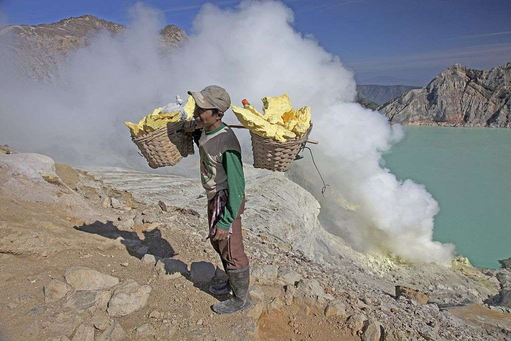 Cet homme porte de grandes quantités de minerais de soufre extraites du solfatare. Derrière, on peut observer le lac du cratère, considéré comme le plus acide au monde. © Jean-Marie Hullot, Wikipédia, cc by sa 2.0