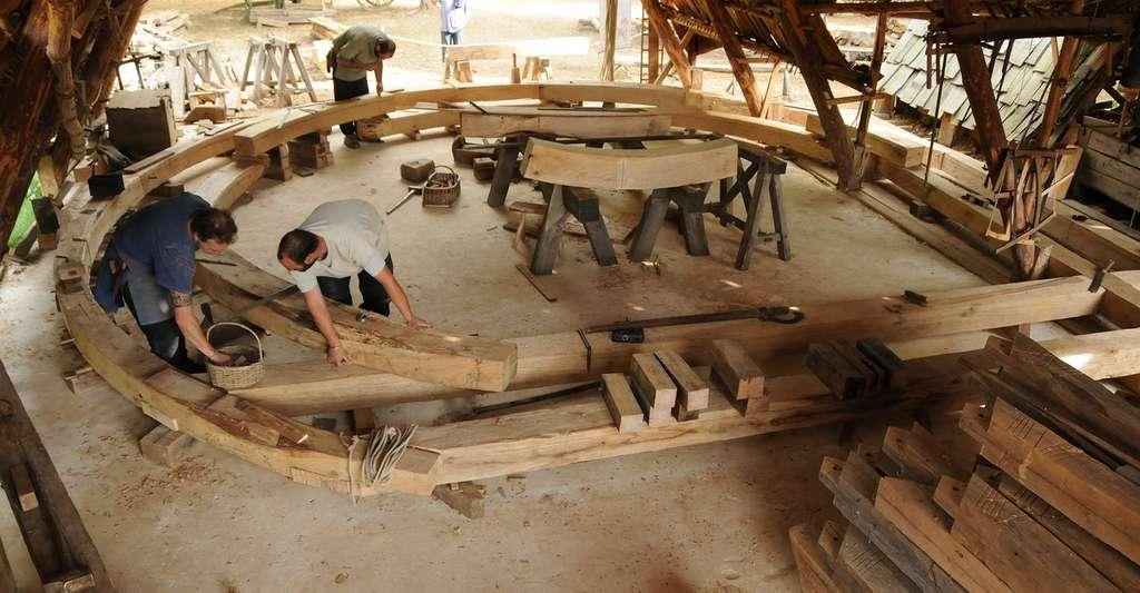 Charpentiers en train de tailler les éléments de la charpente de la tour de la chapelle, 2017. © Clément Guérard, Guédelon, tous droits réservés