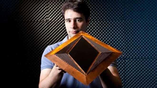 Nathan Landry, membre de l'équipe et coauteur de l'article, présente son dispositif d'invisibilité, sur lequel sont visibles, à gauche et à droite, les fibres de verre dopées au cuivre. La zone d'invisibilité est au centre. © Duke University