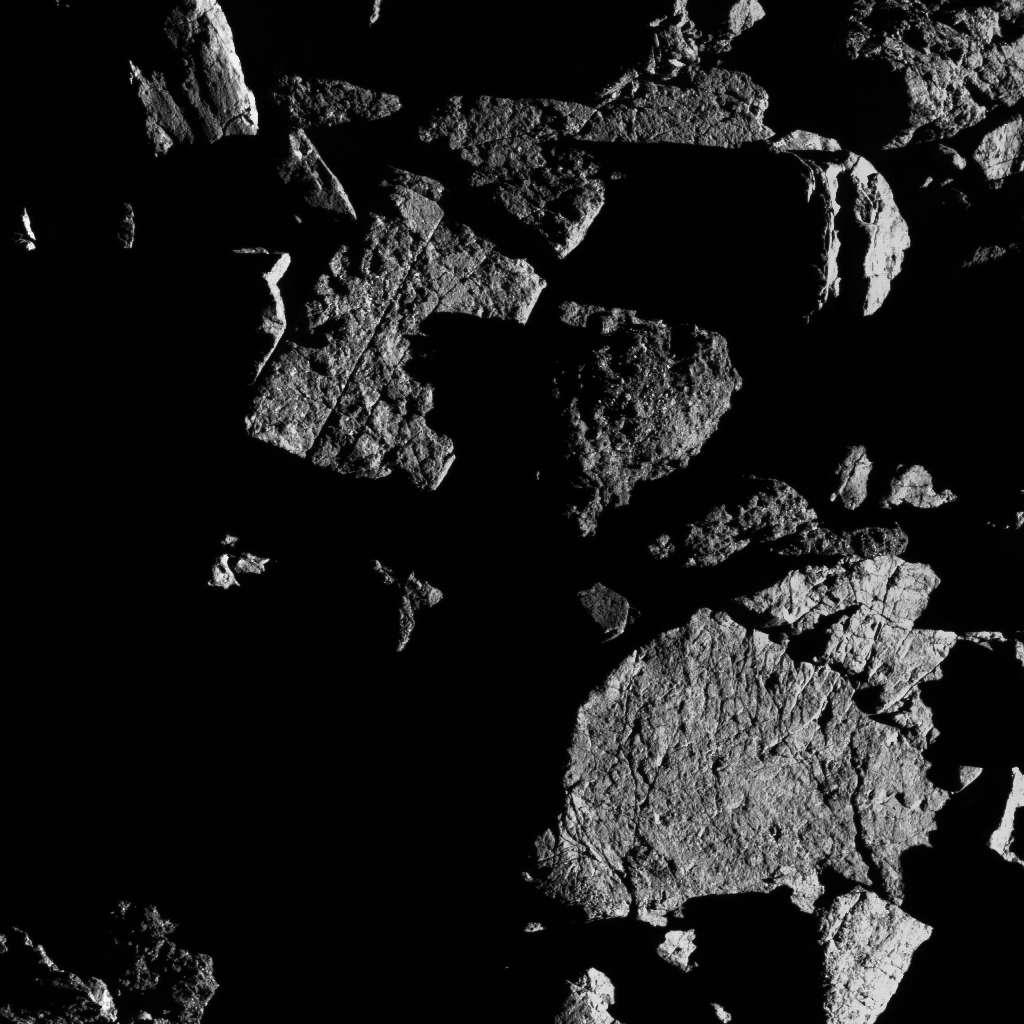 Groupe de gros rochers situés juste au nord de la région équatoriale de Bennu. Le rocher en bas à droite montre des signes d'exfoliation, où la fracturation thermique a probablement provoqué l'écaillage de petites couches minces de la surface du rocher. © Nasa, Goddard University of Arizona