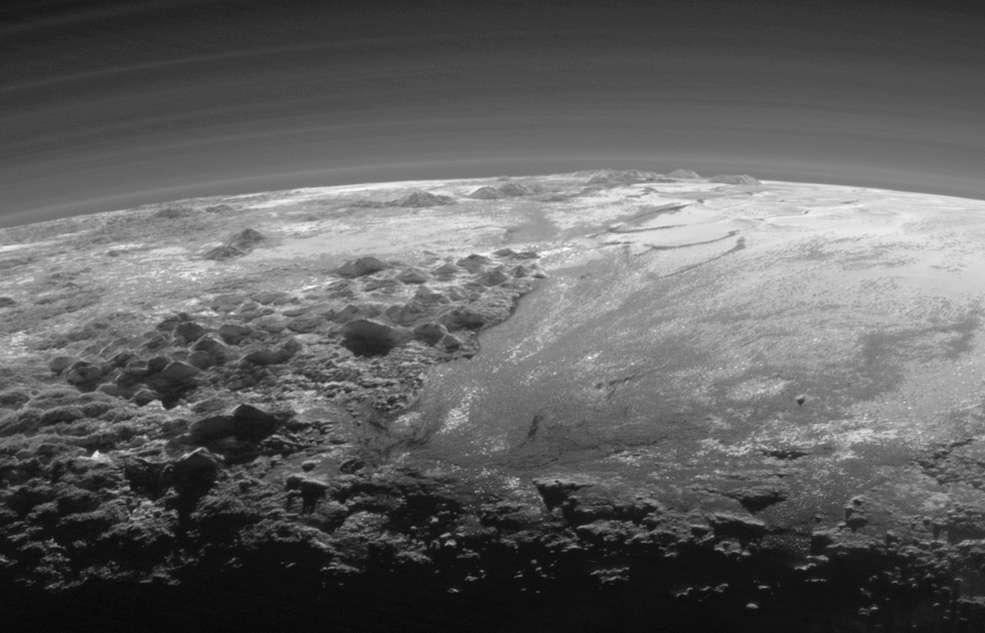 Vue détaillée de la plaine Spoutnik (partie droite) et de ses glaciers coulants. À gauche et en bas, Norgay Montes. Certaines de ces montagnes culminent à 3.500 m. À l'horizon, les reliefs de Hillary Montes. Les brumes sont rétroéclairées par le Soleil couchant. L'image couvre une région qui s'étend sur 380 km. Téléchargez l'image en haute résolution ici (2,2 Mo). © Nasa, JHUAPL, SwRI