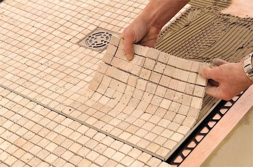 Si vous posez des galets ou de la mosaïque en plaques, pressez du plat de la main pour assurer un bon transfert de la colle. © Schlüter Systems