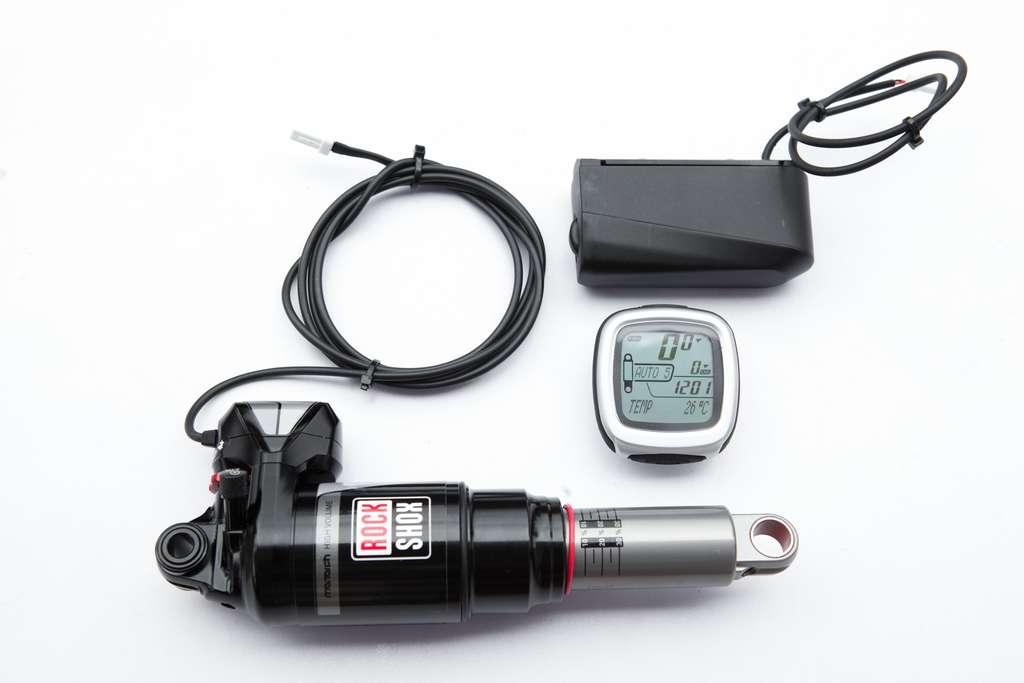 Le kit Ei Shock développé par Lapierre se compose d'un amortisseur arrière sur lequel est greffé un servomoteur, d'une batterie ayant 25 heures d'autonomie, de capteurs (accéléromètre, capteur de cadence de pédalage) et d'un miniordinateur de bord installé sur la potence du vélo qui pilote le système. © Lapierre