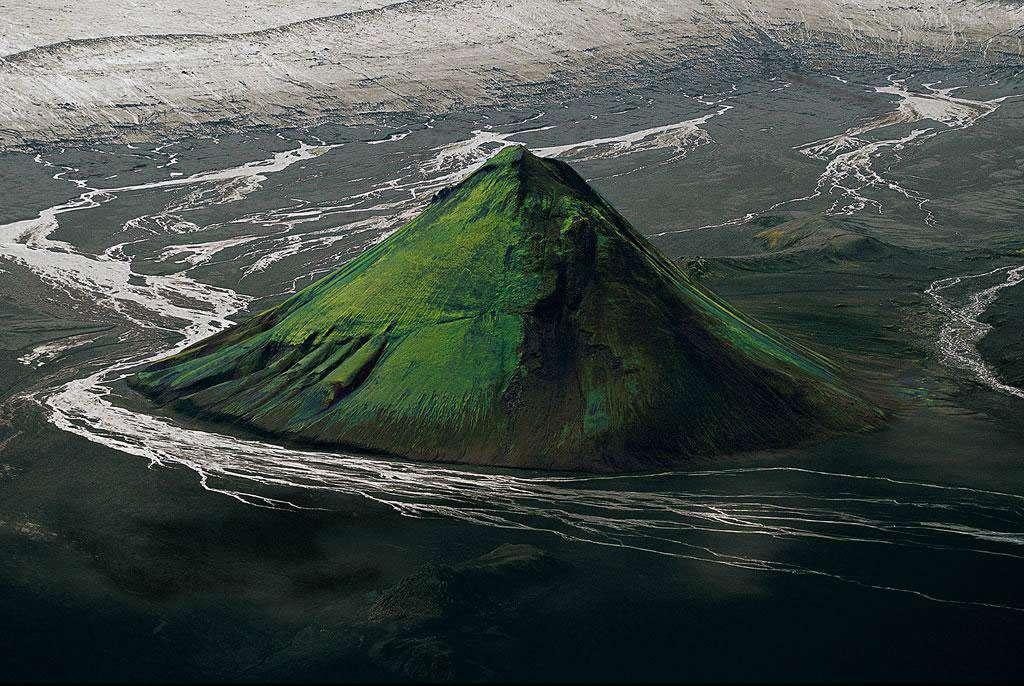 Le Maelifell en bordure du glacier Myrdalsjökull, Islande (63°51' N - 18°13' O). Au sud de l'Islande, ce cône volcanique, constitué de cendres et de projections de lave solidifiées, est né de l'une des nombreuses éruptions survenues sous la calotte du glacier Myrdalsjökull avant que celui-ci ne se retire. Délivré du glacier il y a environ 10.000 ans, le Maelifell est maintenant baigné par les rivières qui s'en écoulent. Son cône parfait, qui s'élève à 200 m au-dessus de la plaine, est recouvert de mousses du genre grimmia qui prolifèrent sur les laves refroidies et dont la couleur varie du gris argent au vert lumineux selon le taux d'humidité du sol. © Yann Arthus-Bertrand - Tous droits réservés