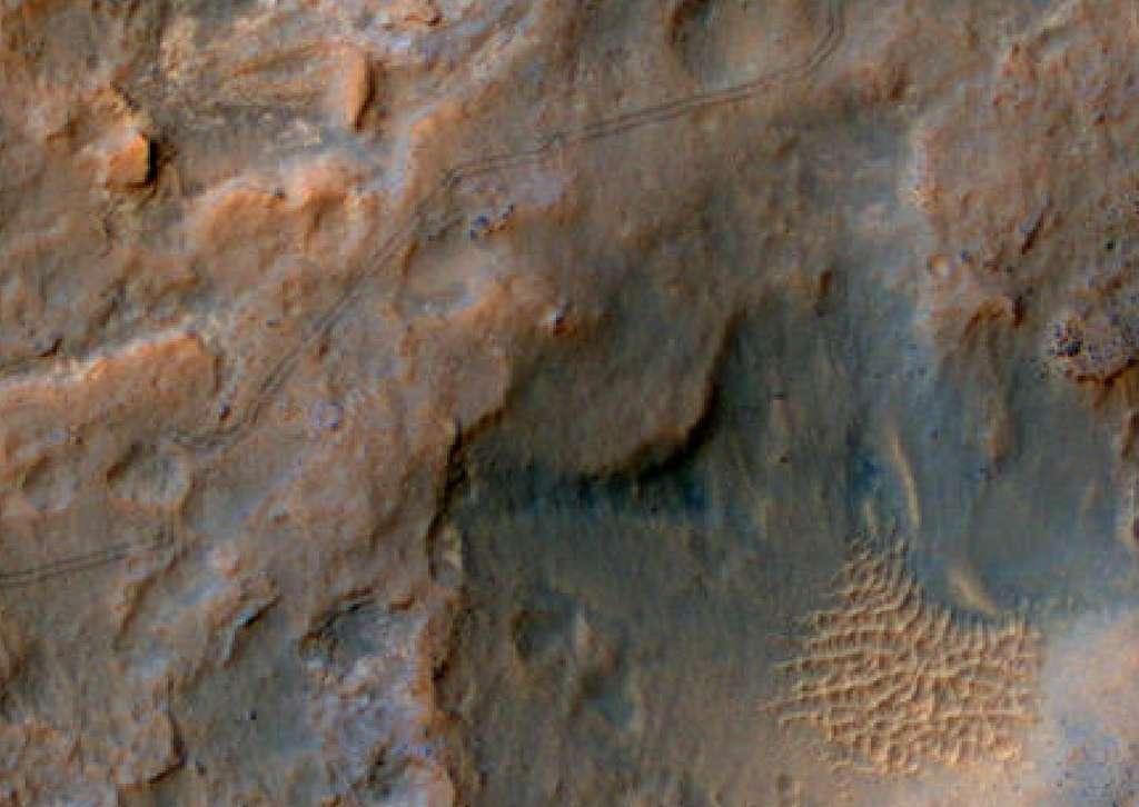 La caméra HiRise, installée sur l'orbiteur MRO (Mars Reconnaissance Orbiter) a saisi le 6 janvier 2014 les traces qu'ont laissées les roues du rover Curiosity, alors en route vers le pied du mont Sharp. Ce robot géologue y cherchera des données sur le passé de Mars, lorsque la Planète rouge avait une atmosphère plus humide et plus chaude. © Nasa, JPL, University of Arizona