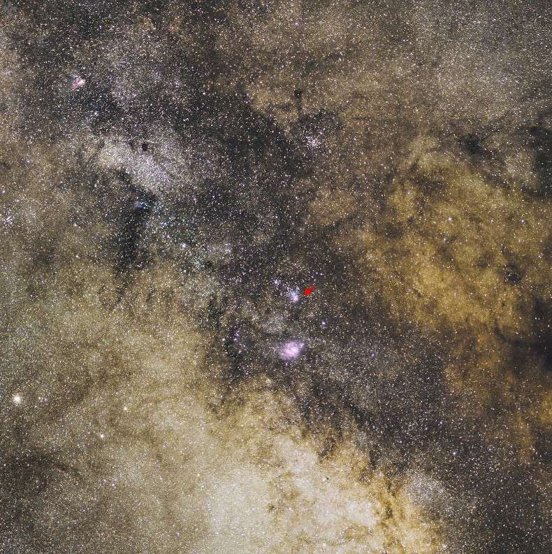 Perdue dans la Voie lactée, la Trifide (flèche rouge) n'est pas la seule nébuleuse visible sur cette spectaculaire image. Crédit Serge Brunier