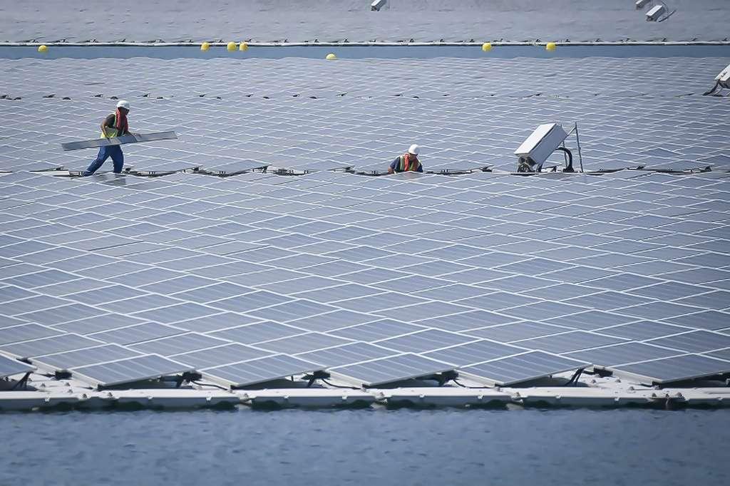 Des techniciens travaillent sur les panneaux photovoltaïques de la centrale flottante O'Megal, le 30 juillet 2019 à Piolenc, dans le Vaucluse. © Gérard Julien, AFP