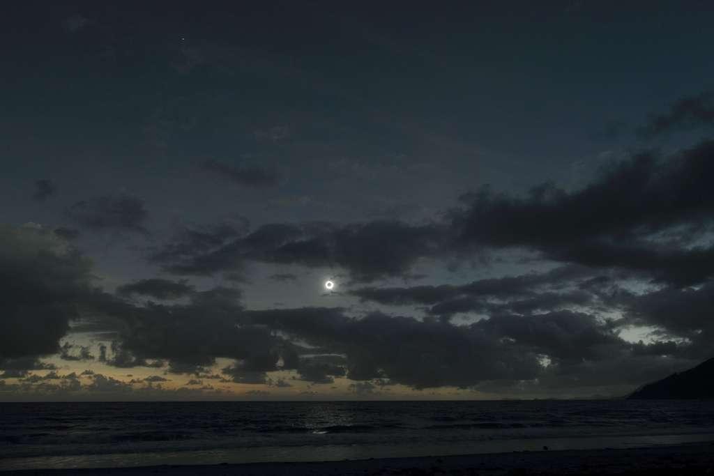 Miracle sur la côte australienne. Les nuages s'écartent pendant les deux minutes que dure la phase totale de l'éclipse solaire. La brillante planète Vénus est également visible plus haut dans le ciel. © Efremidis Yiannis