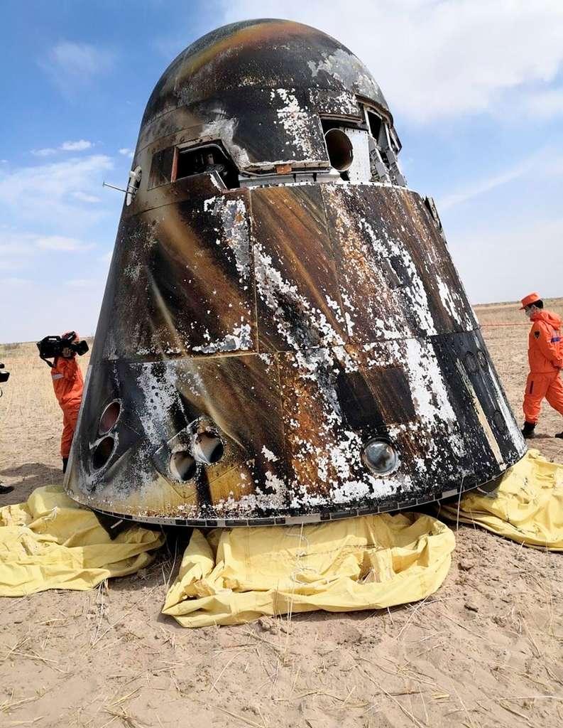 La capsule Shenzhou NG de retour d'orbite après son premier vol de démonstration. Les techniciens chinois présents sur le site permettent de se rendre compte de la taille et du volume de la capsule. © CASC