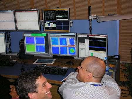 Cliquez pour agrandir. Des physiciens du Cern devant les copies des écrans de contrôle dans la salle de conférence du Globe. Crédit : Laurent Sacco/Futura-Sciences
