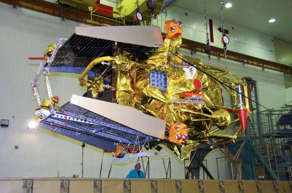 Phobos-Grunt en position horizontale. Le module de retour et la capsule de rentrée atmosphérique sont visibles à gauche, logés au sommet de la sonde, entre les deux panneaux solaires. Quant au module chinois, peu visible à l'image, il se situe sous la sonde, coincé entre les pieds. © Roscosmos