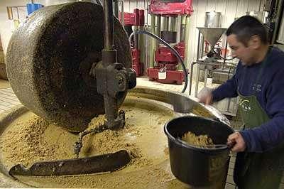 Les cerneaux sont d'abord broyés à la meule, une impressionnante roue en pierre permettant d'obtenir après 40 minutes une pâte © Toute reproduction et utilisation interdites