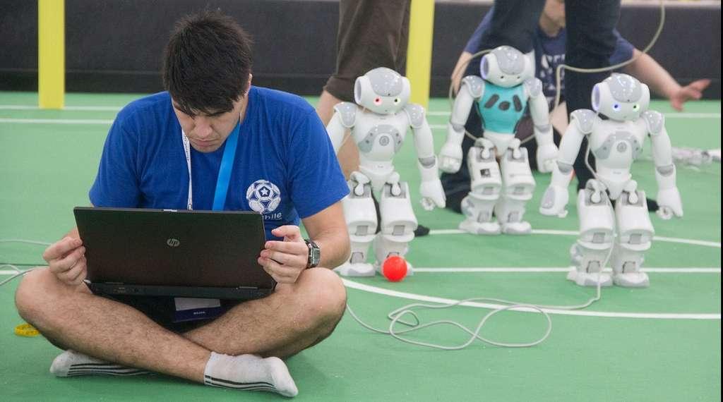 Un coach prépare son équipe de robots humanoïdes pour un match de football. En arrière-plan, se tiennent plusieurs exemplaires du robot Nao conçu par la société française Aldebaran Robotics. © Valdecir Becker/RoboCup/UFPB
