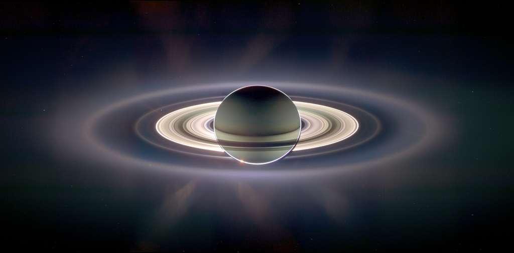 Sur cette image prise à contrejour, on voit la poussière autour de Saturne diffusant la lumière du Soleil. Surtout, en haut à gauche de la partie la plus brillante des anneaux de Saturne, on peut voir un point bleu pâle selon l'expression de Carl Sagan. C'est la Terre ! © N.A.S.A, JPL