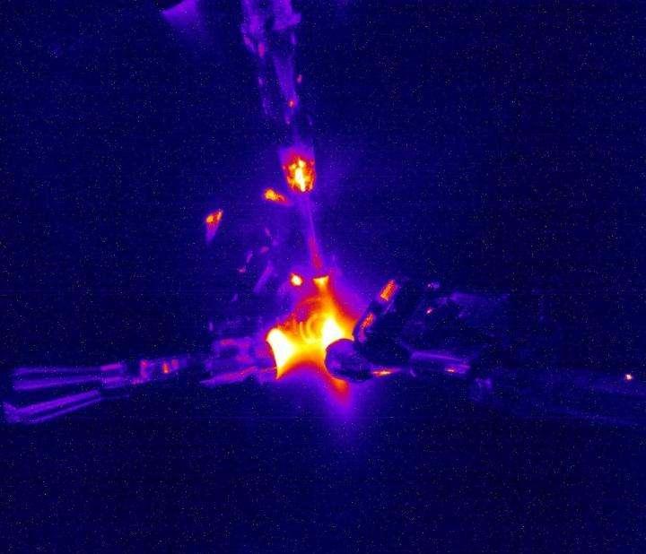Une image de l'expérience avec fusion de noyaux d'hélium 3 à rapprocher de celles dans la vidéo de l'article ci-dessous. Les conditions très chaudes et très denses du cœur du Soleil sont créées par la compression d'une petite capsule en plastique remplie de gaz à une pression 10 fois supérieure à la pression atmosphérique à l'aide 192 faisceaux laser puissants. Certains des faisceaux laser focalisés apparaissent en haut et à gauche de l'image.© Don Jedlovec, LLNL