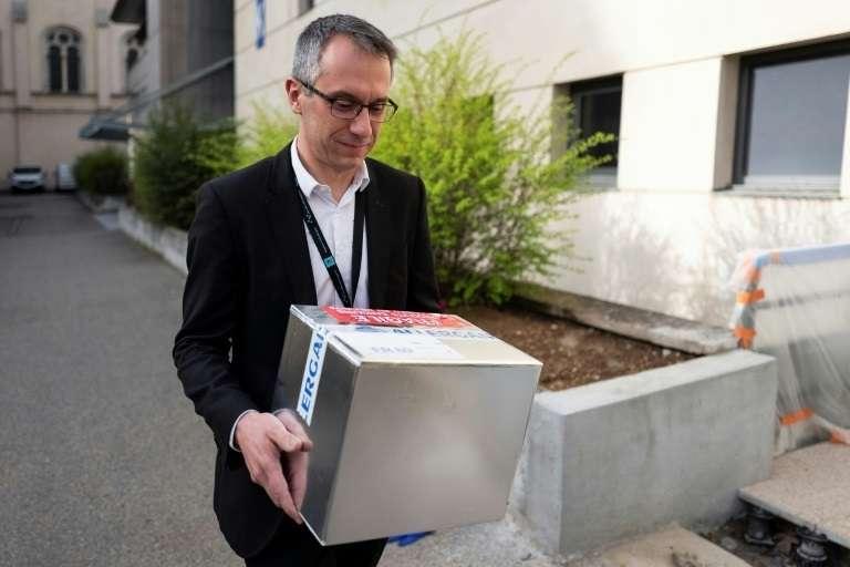 Le professeur Tristan Ferry porte des boîtes contenant des virus phages le 8 mars 2019 à l'hôpital lyonnais de la Croix-Rousse. © Romain Lafabregue – AFP
