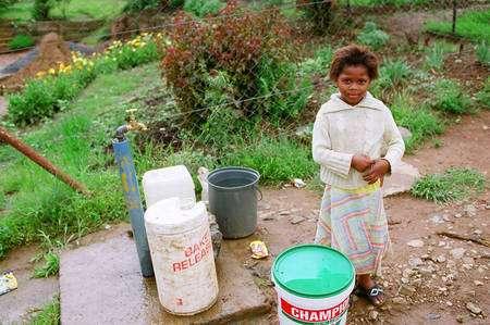 Cette fillette d'Afrique du Sud profite d'un robinet installé dans sa communauté. Auparavant, les habitants devaient aller chercher l'eau plusieurs fois par jour dans une rivière polluée. © Lionel Goujon et Gwenael Prié