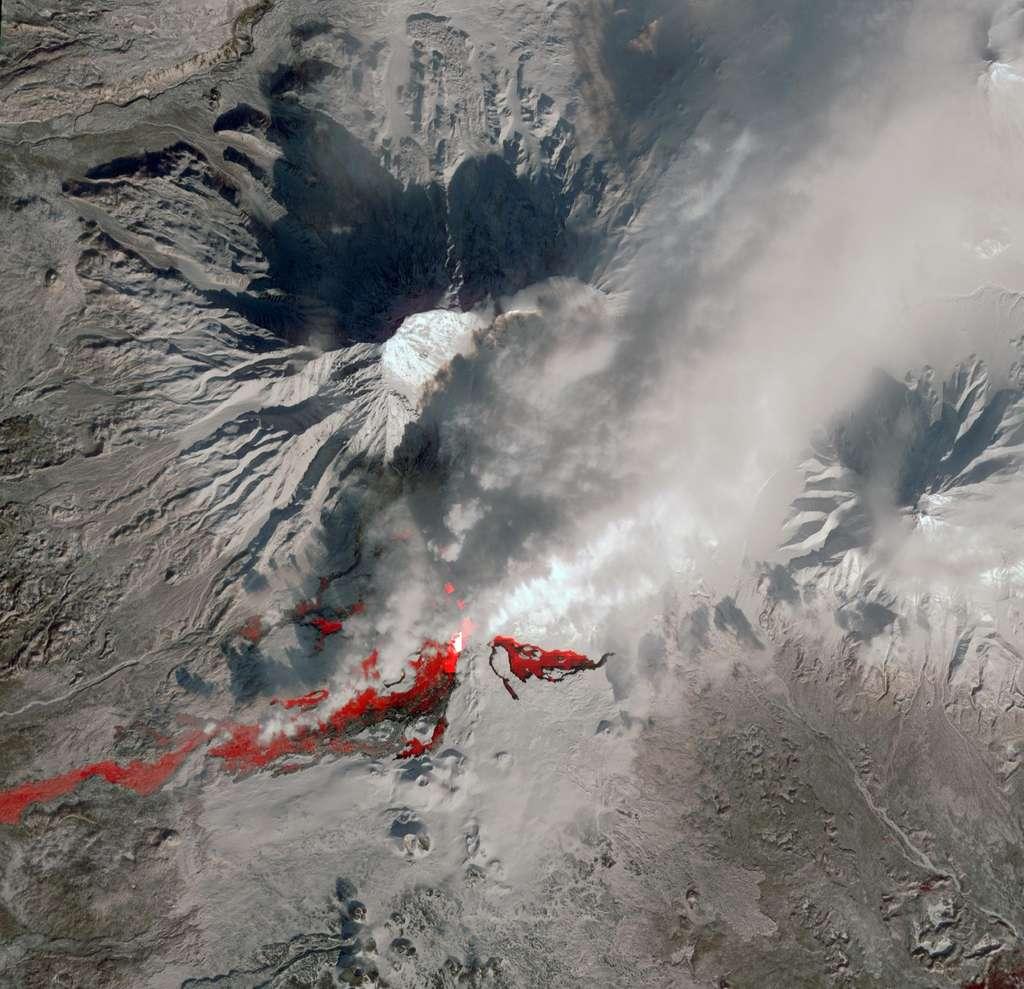 Image saisie le 14 février 2013 par l'instrument Aster du satellite Terra (Nasa), sensible à 14 bandes spectrales du visible à l'infrarouge. Elle couvre une zone de 17 km par 28,6 km, centrée sur le volcan Plosky Tolbatchik, en éruption depuis novembre 2012. On remarque le panache blanc, composé de vapeur d'eau et de cendres. La coloration rouge indique l'anomalie thermique, repérée dans les bandes infrarouges, où le sol est plus chaud que les environs, signifiant que la lave n'est pas loin en profondeur. © Nasa, GSFC, Meti, Ersdac, Jaros, U.S.-Japan Aster Science Team